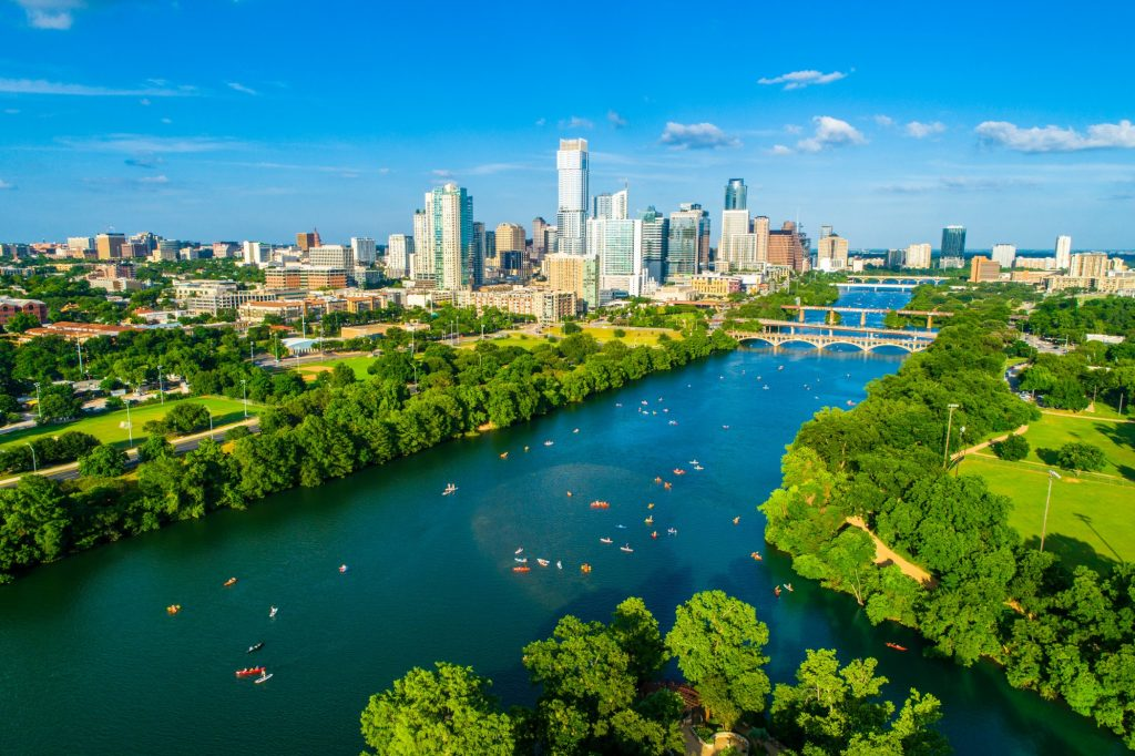 Town Lake Kayaker Crowd as Summer Holidays Pack Summer fun at Lady Bird Lake aerial drone View Downtown Skyline Background